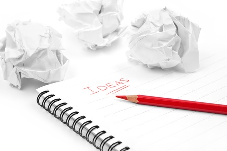 wads: Creativity problems. Blank sheet of paper, red pencil, word Ideas and crumpled paper wads
