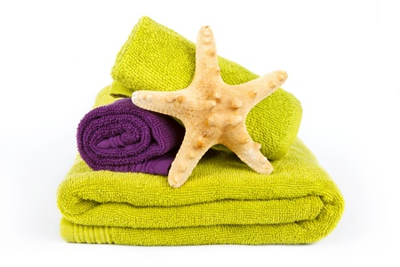 Starfish on stack of colorful towels on a white background photo