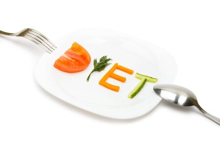 White plate with word diet composed of slices of different fruits and vegetables photo