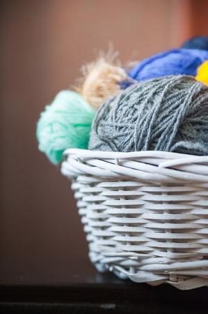 tejido de lana: Colorful yarn balls in wicker basket isolated on white Foto de archivo