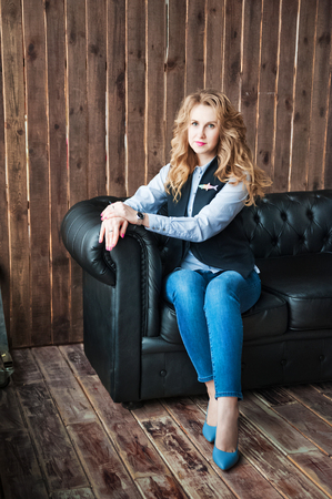 red sofa: A beautiful girl in a blue shirt and a black jacket. Girl with beautiful blond curls on a black leather sofa on a wooden wall background. Business Girl