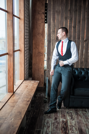 lost in thought: Portrait of a man in a white shirt, red tie and black vest on the background of a brick wall and a large window. Portrait of a man who is lost in thought, waiting and looking at the camera