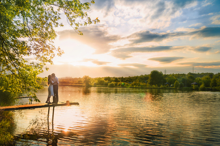 Beautiful summer picture on the nature by the river. A loving couple is standing on the pier on a sunset background. Archivio Fotografico