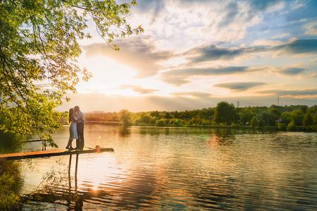Mooie zomerse foto van de natuur aan de rivier. Een liefdevol paar staat op de pier op een zonsondergang achtergrond.