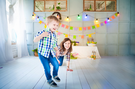 Merry Easter picture of mother and baby boy. A woman plays with her son in a decorated interior. He runs away from his mother and laughs. Banque d'images