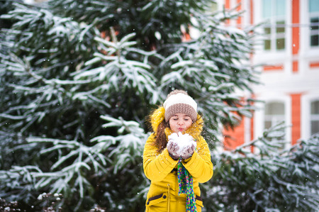 A little girl in a yellow jacket playing with a snow in the winter. The child holds the snow in his hands and blows on it