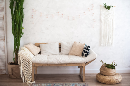 Beautiful spring decorated interior in white textured colors. Living room, beige sofa with a rug and a large cactus. Stock Photo