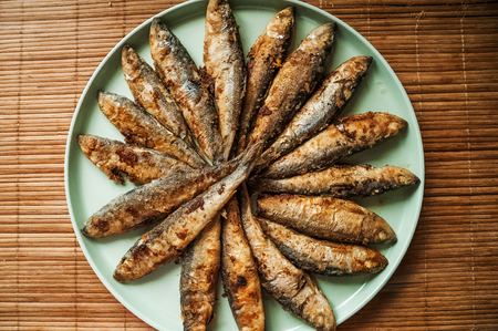 A lot of small fried fish on a large turquoise plate. Salad roast in the form of a circle, the texture of the finished fish. Close-up Stock Photo