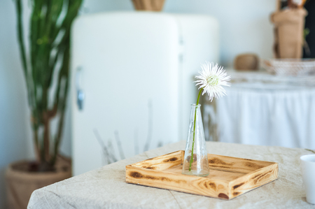 Kitchen in rustic style in summer. Spring light textured kitchen with an old fridge, wooden table. Wooden glass vase with one white flower astra, chamomile