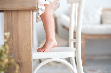 Baby little feet, feet on a white wooden kitchen chair in a rustic style, a chef, a loft