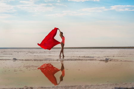 Slender girl on the salt lake of Elton, Volgograd region, Russia. Lake Elton. A girl in a red bathing suit and pareo, the fabric develops in the wind. Salt lake, sea, mud, minerals Foto de archivo