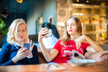Two young women in a cafe at a table. Visitors to the restaurant take pictures of themselves on the phone. Focus on phones
