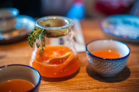 Summer tea in a large pot with a sprig. Tea with mango and orange on the table in a cafe