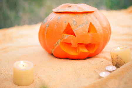 Carved pumpkin on a background of yellow plaid and green grass. Funny and scary muzzle of pumpkin and set candles. Natural texture of pumpkins. Place and background for text Banco de Imagens
