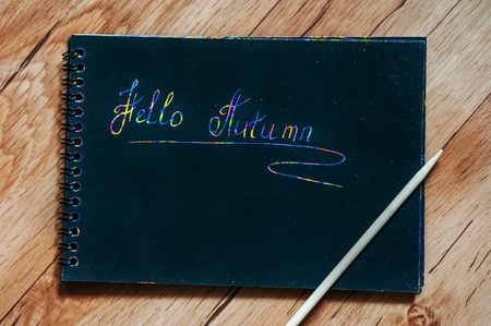 Childrens engraving on a brown wooden table. On the engraving plate is written hello autumn. Concept of autumn