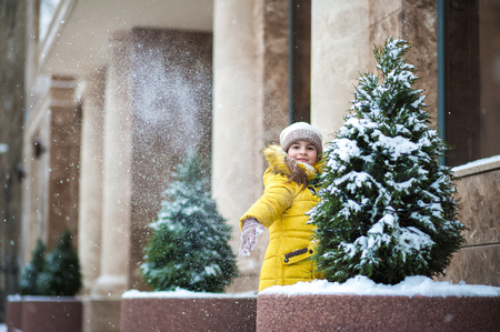 A little girl plays in the winter outside. The girl throws snow, sculpts snowy woman, rejoices in the snow Banque d'images