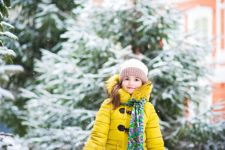A girl in a yellow jacket in the winter rejoices in the snow Children's winter holidays