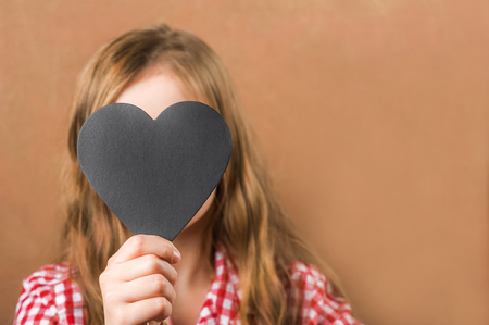 Girl and black slate heart. The girl builds a physiognomy, a grimaces and a heart for an inscription. Valentine's Day concept, close-up and copy space Standard-Bild - 116786443