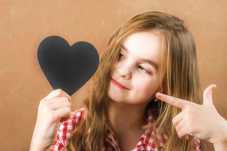Girl and black slate heart. The girl builds a physiognomy, a grimaces and a heart for an inscription. Valentine's Day concept, close-up and copy space Standard-Bild - 116786444