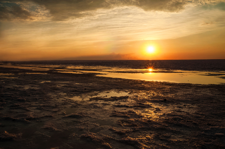 Beautiful natural textural background on the lake, river. Salt lake Elton, Russia, sunset on the water