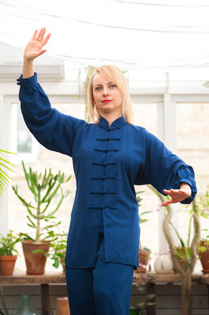 Chinese martial arts tai chi. Woman practicing Taijiquan discipline in a greenhouse with flowers.