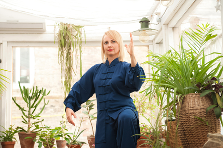 Chinese martial arts tai chi. Woman practicing Taijiquan discipline in a greenhouse with flowers. Stock Photo