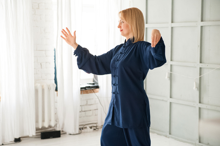 Chinese martial arts tai chi. Woman practicing Taijiquan discipline in blue kimono.