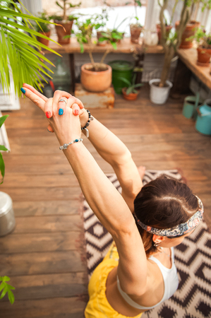 Girl practicing yoga close up and copy space. Woman in yoga asanas in a greenhouse with flowers. Asana hands