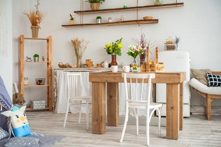 Mesa de madera en una luminosa cocina de estilo rústico. Estilo escandinavo en la cocina. Foto de archivo