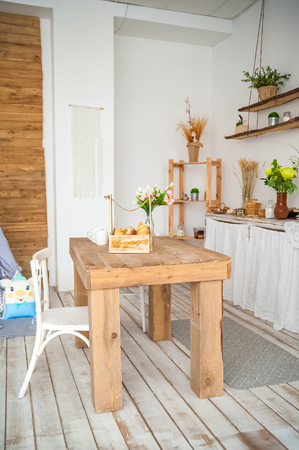 Wooden table in a bright rustic-style kitchen. Scandinavian style in the kitchen.