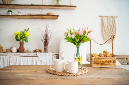 Breakfast cups and fruit. Spring tulips on the table. Wooden table in a bright rustic-style kitchen. Scandinavian style in the kitchen.