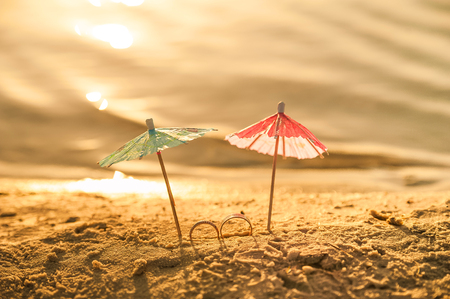 The concept of wedding at sea. Miniature cocktail umbrellas and wedding rings on the beach at sunset
