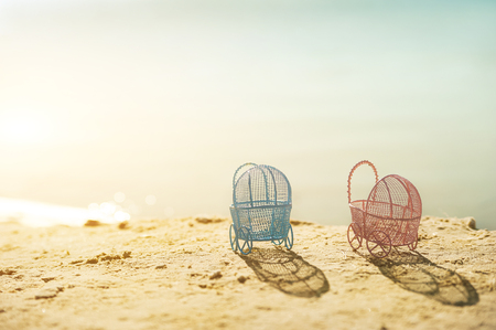The concept of pregnancy at sea. Pink and blue miniature strollers on the beach at sunset