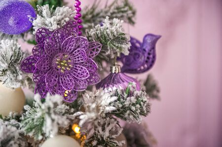 Christmas picture in pink, purple, neon color close up. Scandinavian style of decorating the Christmas tree. Christmas toys such as birds, flowers, garlands, copy space. Stockfoto