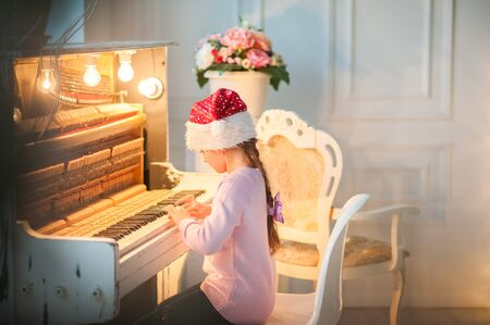 Little girl in santa hat is waiting for the new year. The girl on christmas Stock Photo