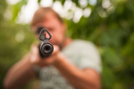 Concept of shooting, hunting close-up. A man shoots from a pneumatic weapon in nature close-up. Air rifle parts and copy space.