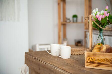 Breadboard in a rustic style. Breakfast, bread, white cups in the Scandinavian cuisine.