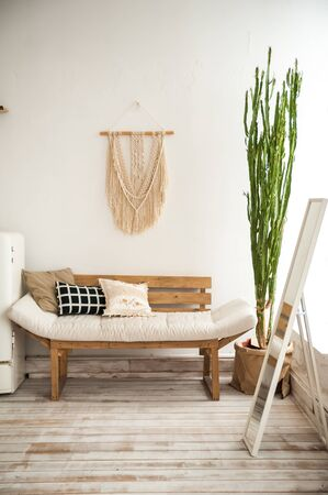 Living room with a rustic sofa. Made from macrame on the wall, a large cactus in the room. Details of a light Scandinavian interior.