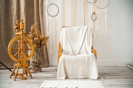 Living room with a rustic armchair. Retro chair, spindle, macrame on the wall in the room. Details of a light Scandinavian interior.