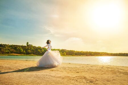 Romantic wedding couple on the shore. The bride runs along the shoreline against the backdrop of a lake or sea.