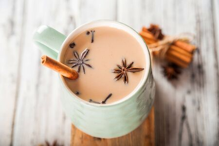 Details of still life in the home interior living room. Beautiful Cup of tea with milk, star anise, cinnamon on a wooden background. Cozy autumn-winter concept. Masala is a traditional hot spicy drink of the winter season with cinnamon, fennel, anise and other spices. Thanksgiving holiday celebration recipe. Flat lay.