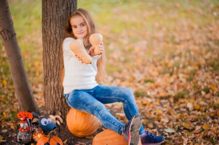 Happy Halloween! Little girl carving pumpkin at Halloween. Dressed up children trick or treating. Kids trick or treat. Toddler kid with jack-o-lantern. Cute little child with a pumpkin in the park.