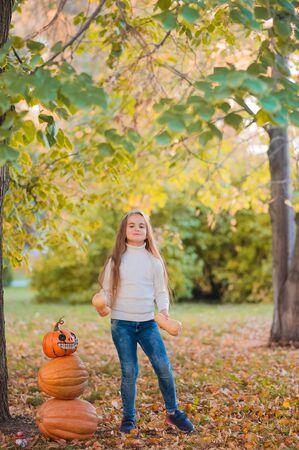 ¡Feliz Halloween! Niña talla de calabaza en Halloween. Niños disfrazados de truco o trato. Truco o trato de los niños. Niño pequeño con jack-o-lantern. Niño lindo con una calabaza en el parque. Foto de archivo