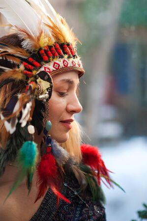 Indian woman hunter. Close-up portrait of beautiful woman in native american costume with feathers. Portrait of a beautiful girl. Native american, Indian woman in traditional dress, posing. native american woman shaman with pikestaff on background of sunset
