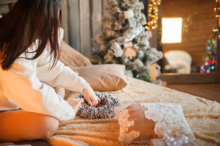 A girl in a white sweater makes a wreath of fir cones. Woman in a bedroom interior in Rustic style for Christmas and New Year. DIY wreath of fir cones.