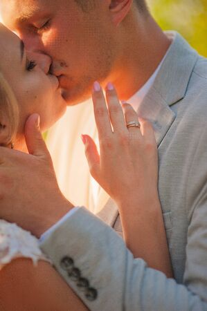 Loving wedding couple hugs and kisses in the summer at sunset. The concept of romantic relationship, idyll. Close-up kiss and tender hugs.