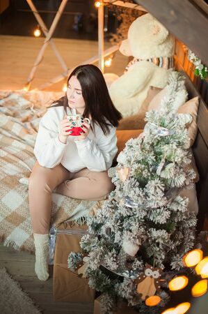 Christmas morning concept at home in the bedroom. Girl on the bed against the background of the Christmas tree in anticipation of the New Year. Stockfoto