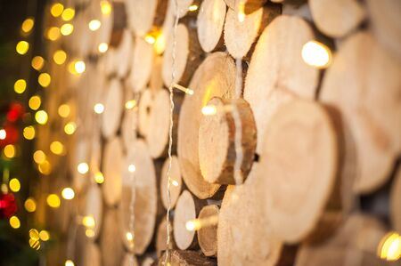 Background of natural wooden saw cuts and christmas garland. Christmas background made of wood and lights for text close-up and copy space.
