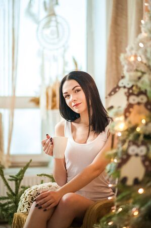 Beautiful girl in the morning with a cup in the New Years interior. Woman at home at Christmas time in a bedroom in a rustic style near a New Year tree.