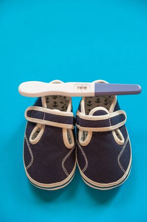 Minimalistic flat lay with baby shoes and a pregnancy test. The concept of pregnancy, motherhood, birth. Booties and a positive pregnancy test on a blue background.